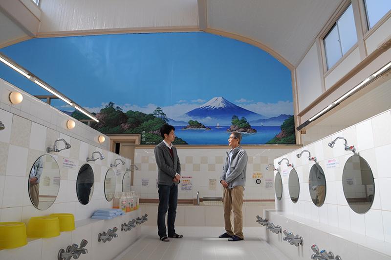 小杉湯店主の平松茂さんと取材ライターと富士山の絵の前にて